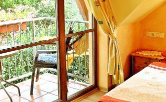 Blick auf Balkon im mediterran eingerichtetem Gästezimmer